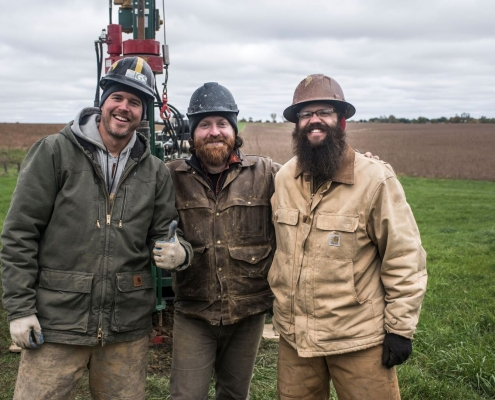 Three men in outdoor winter work clothes pose in front of a drill rig