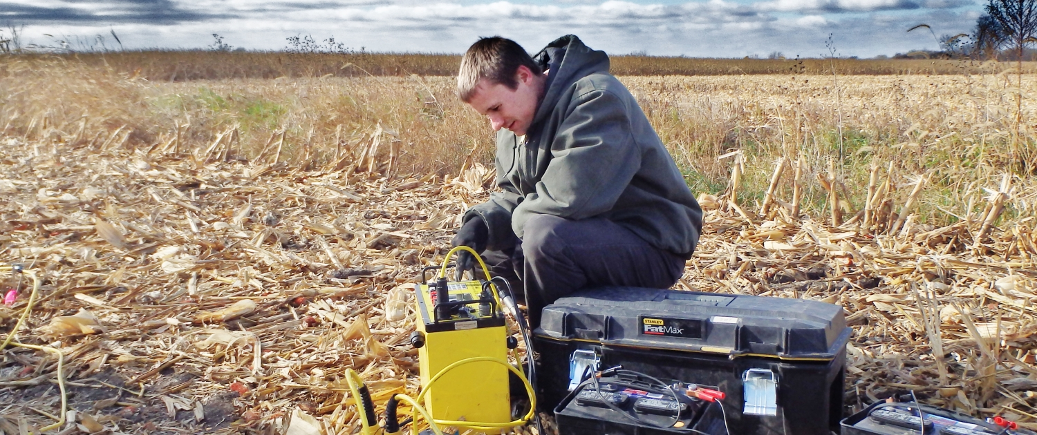 A young man works with equipment in a field of cornstanks