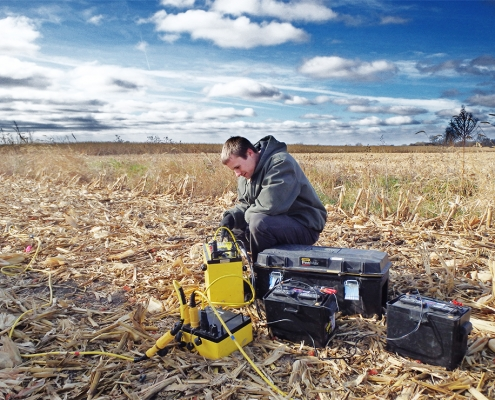 Young man sits ina field of cornstalks working with an electrical resistivity machine.