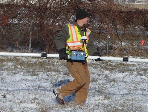 A researcher holding a pipe walks through a field lightly dusted with snow