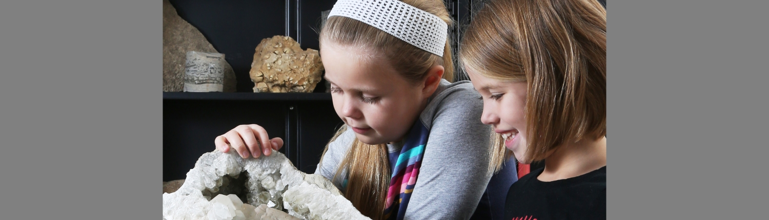 Two young girls examine a huge geode