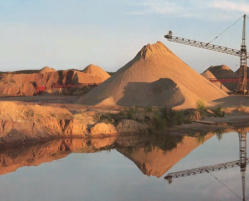 An Iowa quarry with piles of sand and gravel and a large crane, all near the Shell Rock River