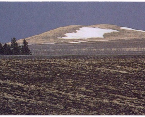 Iowa farm field landscape in winter with a large mound in the background