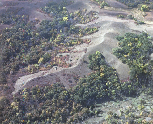 Aerial view of the loess hills with grayish hill crests surrounded by trees.