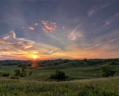 Colorful sunset over a green rolling landscape