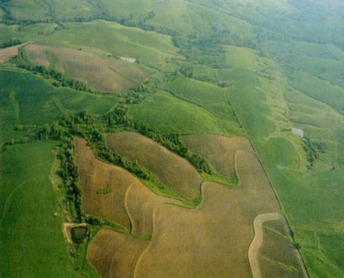 Aerial view of Iowa landscape showing contoured farmlands and green fields