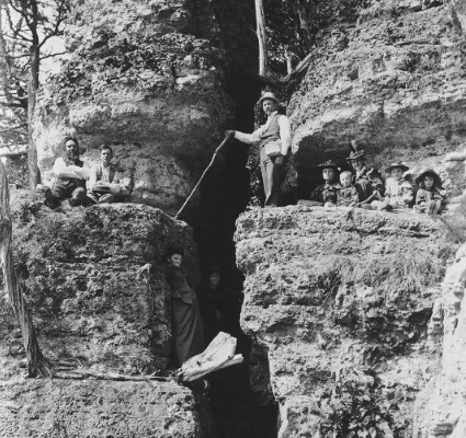 A family rock climbs in Backbone State Park in this circa 1890s, black and white photo