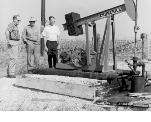 Three men stand near an oil well in this black and white photo.