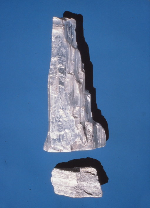 Two chunks of grayish white rock against a blue background