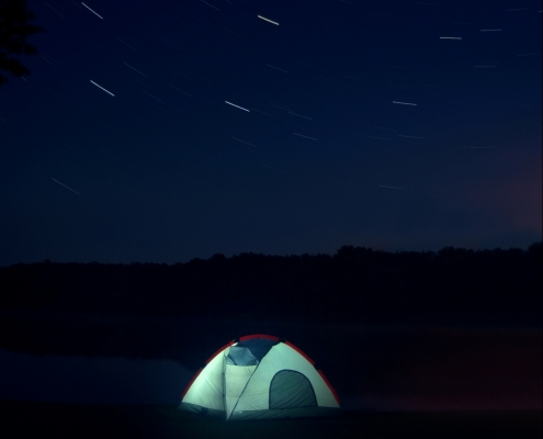An illuminated greenish tent against a midnight blue sky with spinning stars
