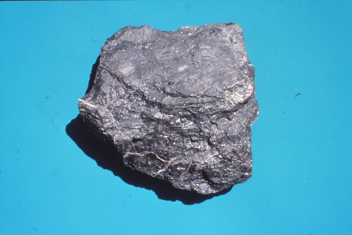 A chunk of black coal against a turquoise background